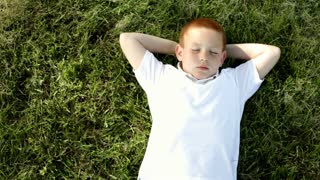 Young boy relaxing laying in grass