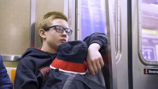Young boy riding subway train in city 4k