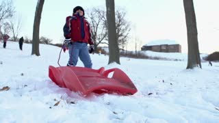 Young boy running up hill with sled