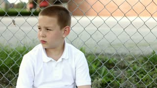 Young boy sitting against fence upset