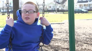 Young boy sitting on swing looking at camera