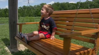 Young Boy Swinging on Hanging Bench
