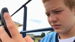 Young boy using cell phone texting with focus on hands 4k