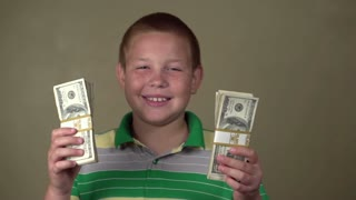 Young boy with stacks of money smiling