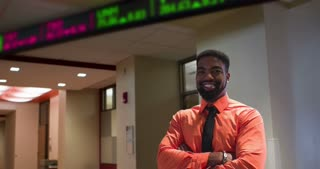 Young businessman standing in front of stock ticker 4k.