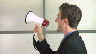 Young businessman yelling into mega phone