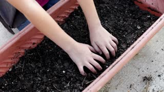 Young child digging through flower bed soil