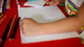 Young child drawing house with colored pencil
