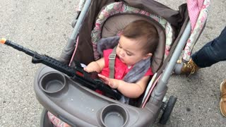 Young child in stroller playing with toy gun