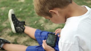 Young child playing on cell phone in grass