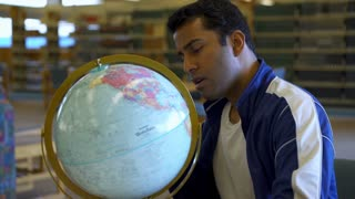 Young college student exploring world globe in library 4k
