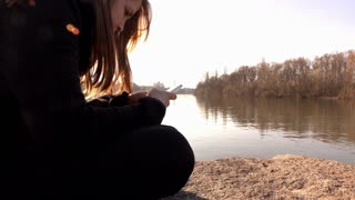 Young female on rock near river using cell phone 4k