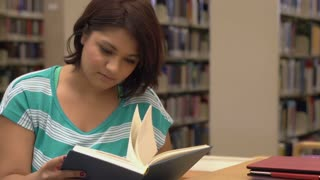 Young female reading book at library