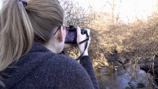 Young female taking picture out in nature 4k