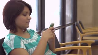 Young female texting in waiting area