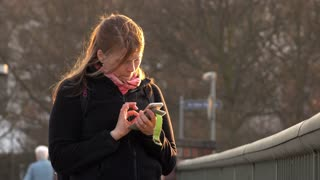 Young female using smart phone to look up information panning shot 4k