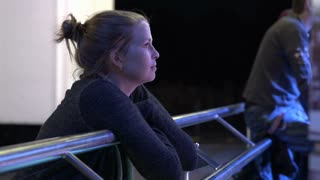 Young female watching carnival ride at night 4k