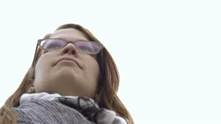 Young female with glasses looking into distance 4k