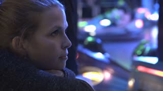 Young girl at carnival watching bumper cars 4k