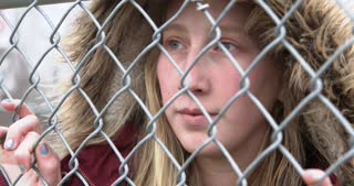 Young girl looking through fence with sadness in eyes 4k