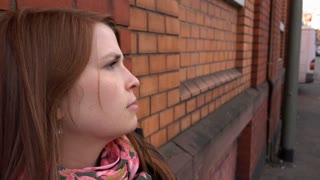 Young girl looking troubled leaning against brick wall on city street 4k