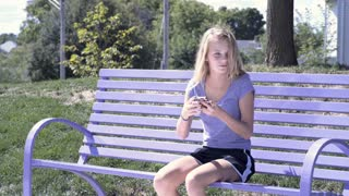 Young girl playing game on cell phone in park 4k