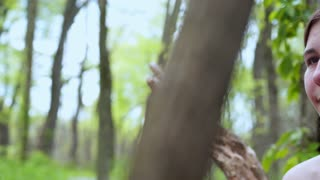 Young girl sitting in forest pan shot 4k
