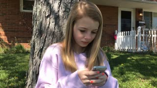 Young girl sitting in front yard of home texting 4k