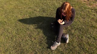 Young girl sitting in grass on cell phone tracking shot 4k