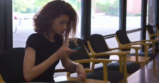 Young girl sitting in waiting area texting 4k
