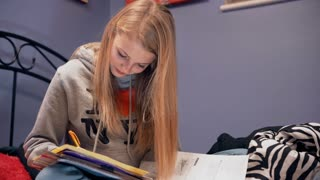 Young girl sitting on bed doing homework 4k