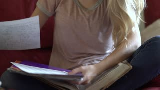 Young girl sitting on couch working on school work 4k