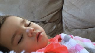 Young girl sleeping on couch with stuffed animal