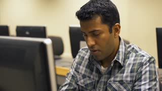 Young Indian male working at computer workstation in lab 4k