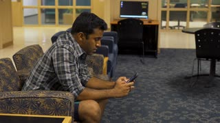 Young Indian man texting in lounge on cell phone 4k