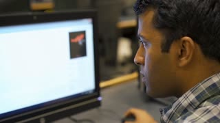 Young Indian man working at computer 4k