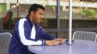 Young male sitting out outdoor table waits for someone to arrive 4k