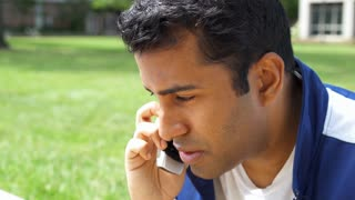Young man from India on cell phone talking outdoors 4k