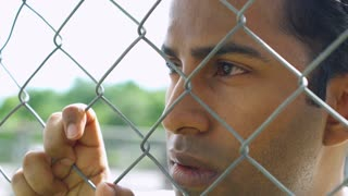 Young man gripping onto fence looks into distance 4k