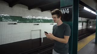 Young man in subway station waiting for train