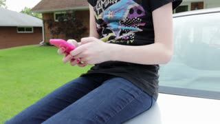 Young teen girl on cell phone texting sitting on car