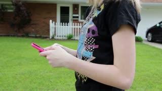Young teen texting and walking through neighborhood