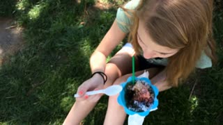 Young teenage girl eating shaved ice snow cone at summer time 4k