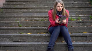 Young woman sitting on stairs reading her book outside 4k