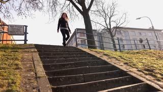 Young woman walking down steps onto path in park 4k