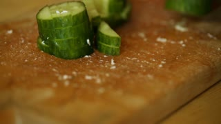 Amateur female cooker cutting cucumber in kitchen