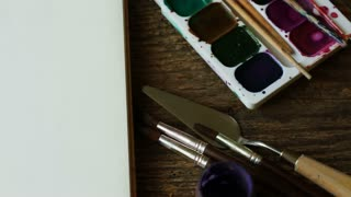 Art of Painting. Painting set: paper, brushes, paints, watercolor, acrylic paint on a wooden background