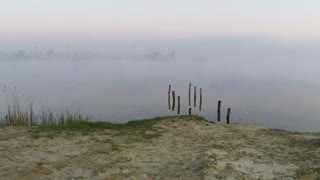 Flying over the misty lake at dawn - aerial survey