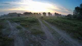 Flying over the misty meadow at dawn - aerial survey