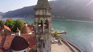 Flying over the old church on the shore of the Bay of Kotor in Montenegro